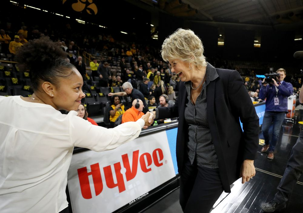 Iowa Hawkeyes head coach Lisa Bluder smiles as she shakes hands with Clemson graduate assistant coach and former Hawkeye Tania Davis before their game Wednesday, December 4, 2019 at Carver-Hawkeye Arena. (Brian Ray/hawkeyesports.com)