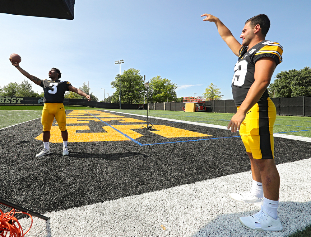 Iowa Hawkeyes wide receiver Nico Ragaini (89) tosses a ball to wide receiver Tyrone Tracy Jr. (3) as a photographer takes pictures during Iowa Football Media Day at the Hansen Football Performance Center in Iowa City on Friday, Aug 9, 2019. (Stephen Mally/hawkeyesports.com)