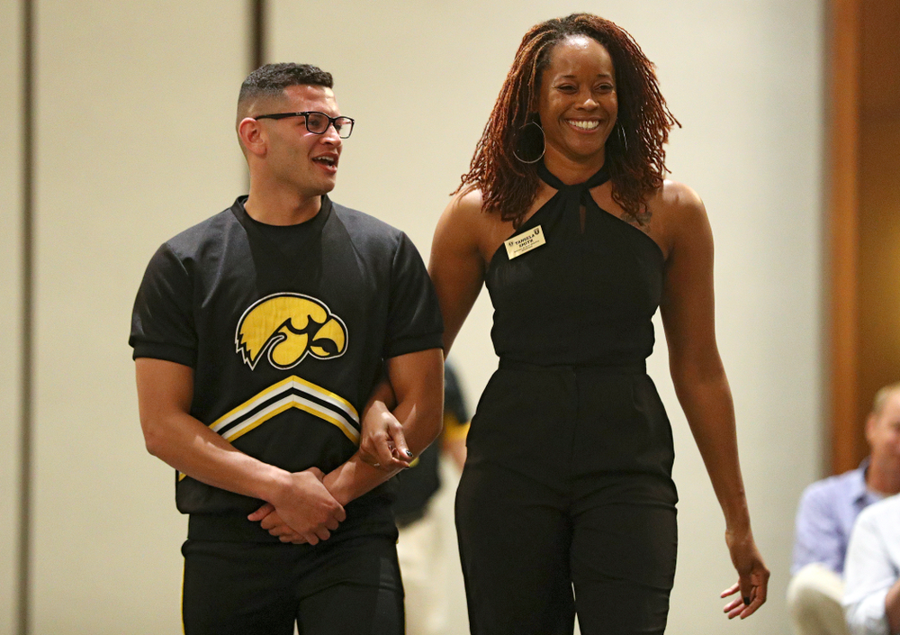 2019 University of Iowa Athletics Hall of Fame inductee Tengela Smith walks to her seat with a Spirit Squad member during the Hall of Fame Induction Ceremony at the Coralville Marriott Hotel and Conference Center in Coralville on Friday, Aug 30, 2019. (Stephen Mally/hawkeyesports.com)
