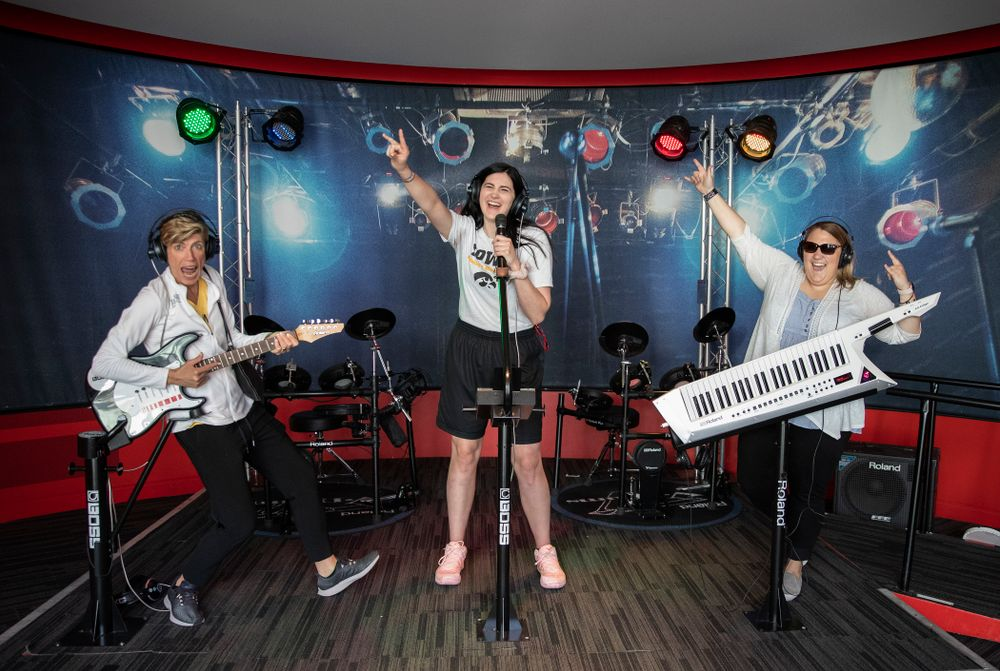 Iowa Hawkeyes forward Megan Gustafson (10) sings as  associate head coach Jan Jensen plays the guitar and SID Brandee Britt plays the keytar  in an exhibit at the Grammy Museum Friday, April 12, 2019 in downtown LA. (Brian Ray/hawkeyesports.com)