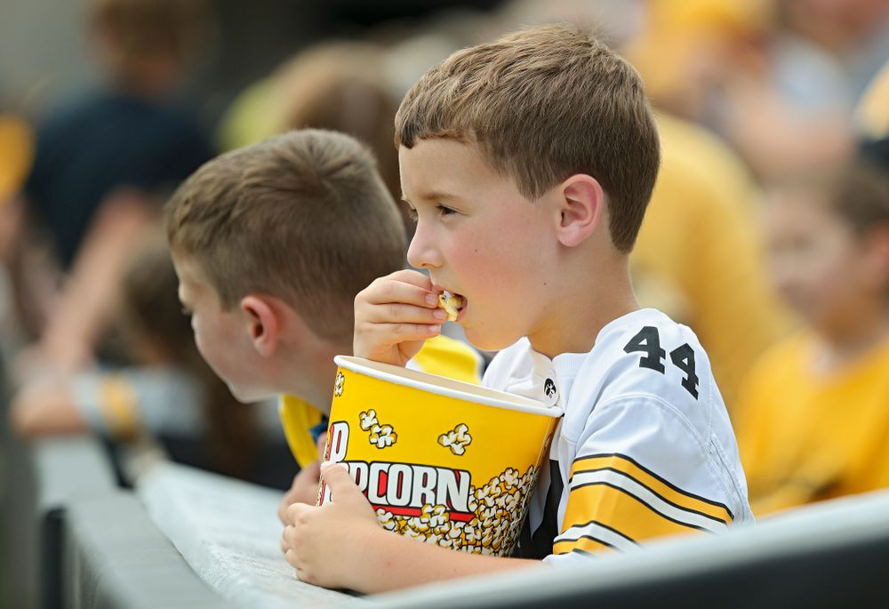 A young fan eats popcorn as he watches Fall Camp Practice No. 8 at Kids Day at Kinnick Stadium in Iowa City on Saturday, Aug 10, 2019. (Stephen Mally/hawkeyesports.com)