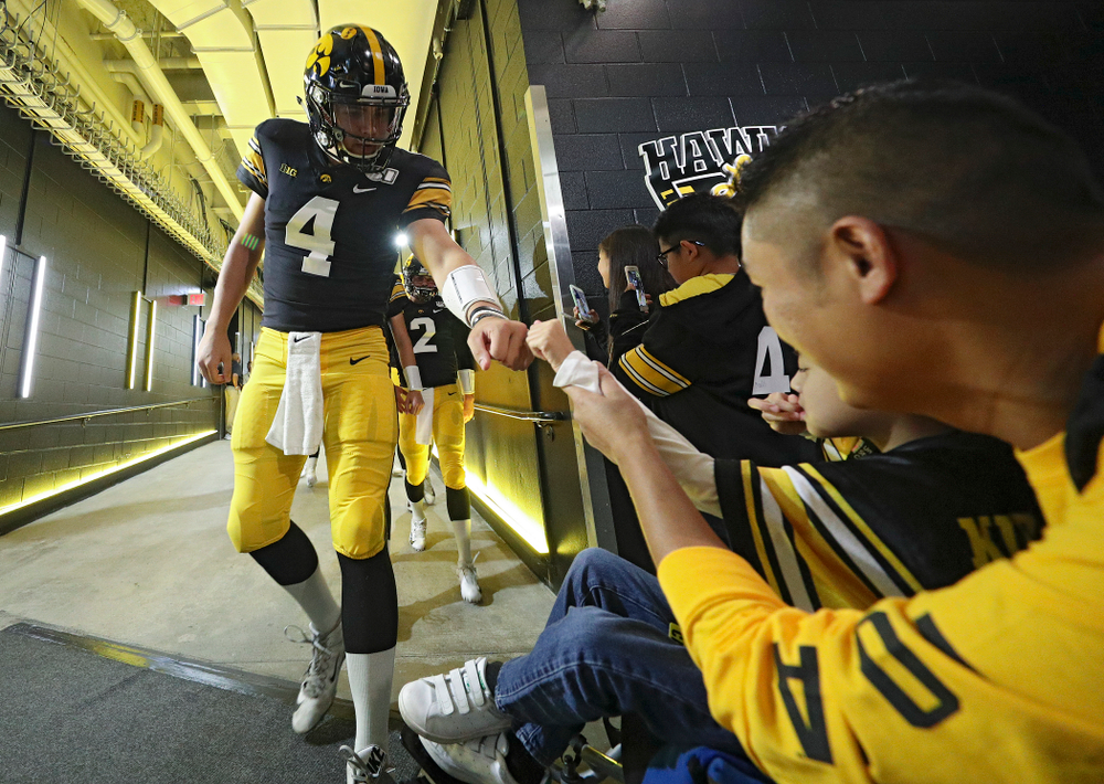 Iowa Hawkeyes quarterback Nate Stanley (4) gives Kid Captain Enzo Thongsoum a fist bump before their game at Kinnick Stadium in Iowa City on Saturday, Sep 28, 2019. (Stephen Mally/hawkeyesports.com)