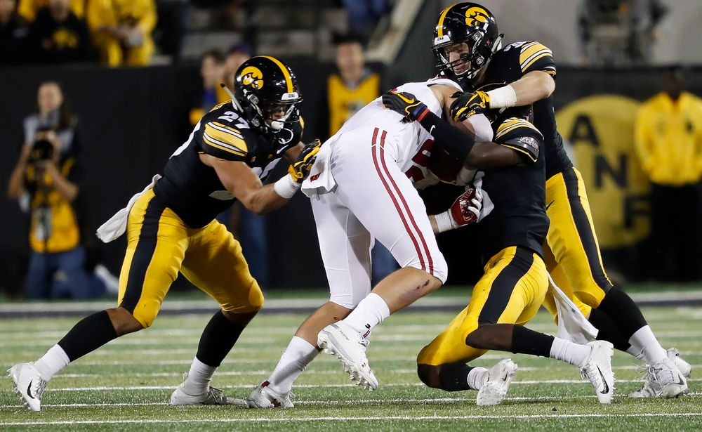 Iowa Hawkeyes defensive back Amani Hooker (27), Iowa Hawkeyes defensive back Jake Gervase (30) and Iowa Hawkeyes defensive back Matt Hankins (8) make a tackle during a game against Wisconsin at Kinnick Stadium on September 22, 2018. (Tork Mason/hawkeyesports.com)