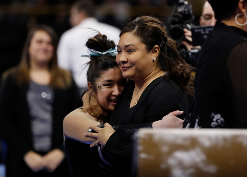 Iowa head coach Larissa Libby hugs  Nicole Chow as she competes on the beam against the Nebraska Cornhuskers