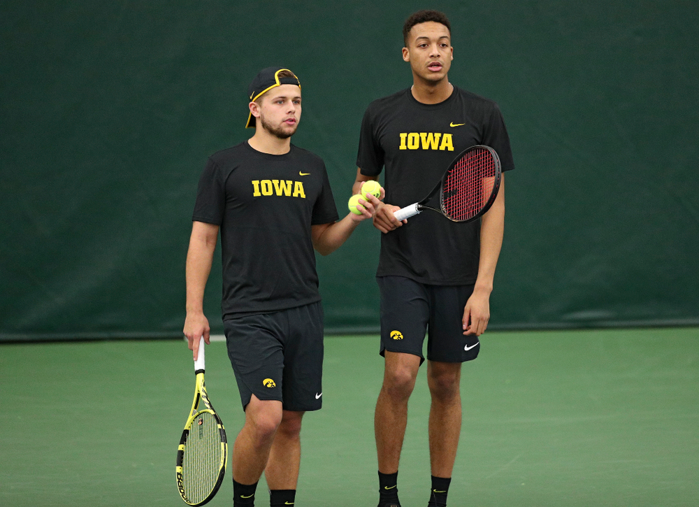 Iowa's Will Davies (from left) and Oliver Okonkwo talk during their doubles match against Marquette at the Hawkeye Tennis and Recreation Complex in Iowa City on Saturday, January 25, 2020. (Stephen Mally/hawkeyesports.com)