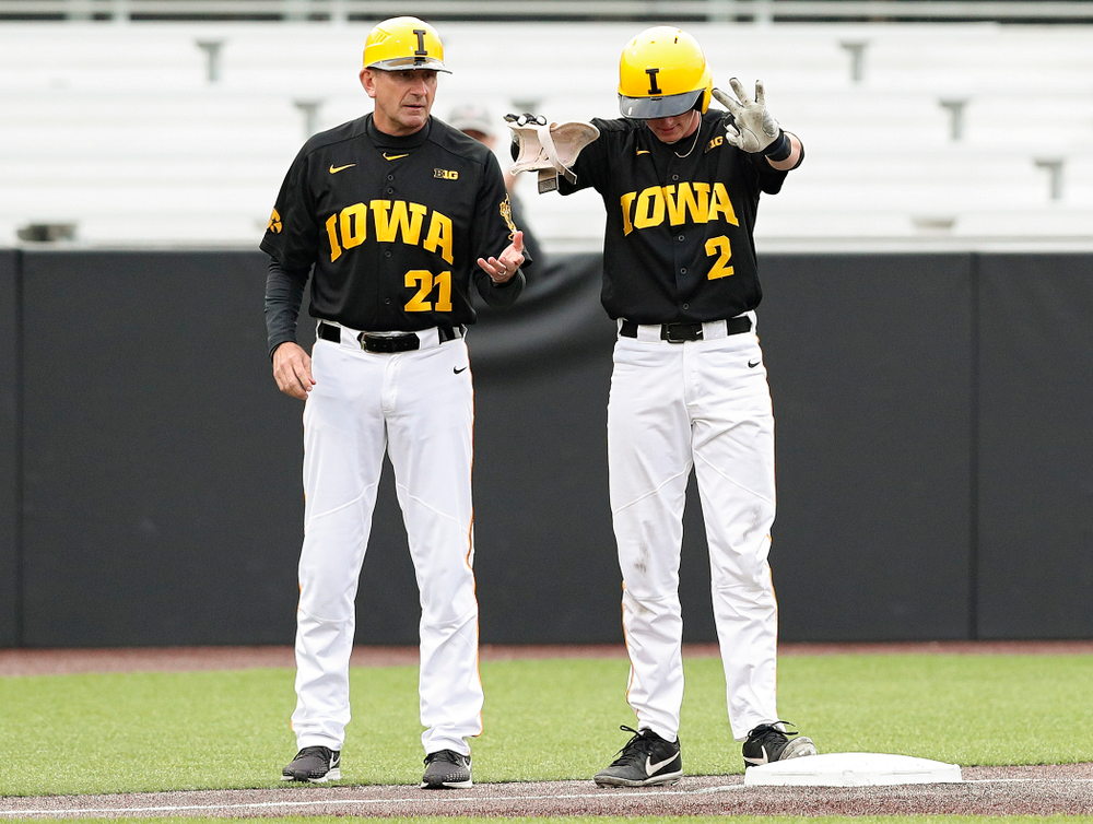Iowa Hawkeyes second baseman Brendan Sher (2) holds up three fingers as he celebrates next to head coach Rick Heller after hitting a triple during the second inning of their game against Western Illinois at Duane Banks Field in Iowa City on Wednesday, May. 1, 2019. (Stephen Mally/hawkeyesports.com)