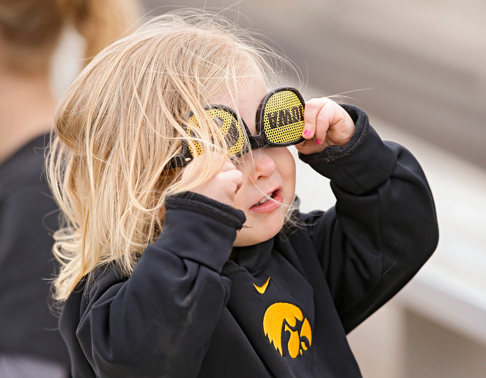 A young fan tries on some sunglasses during the second inning of their Big Ten Conference softball game at Pearl Field in Iowa City on Friday, Mar. 29, 2019. (Stephen Mally/hawkeyesports.com)