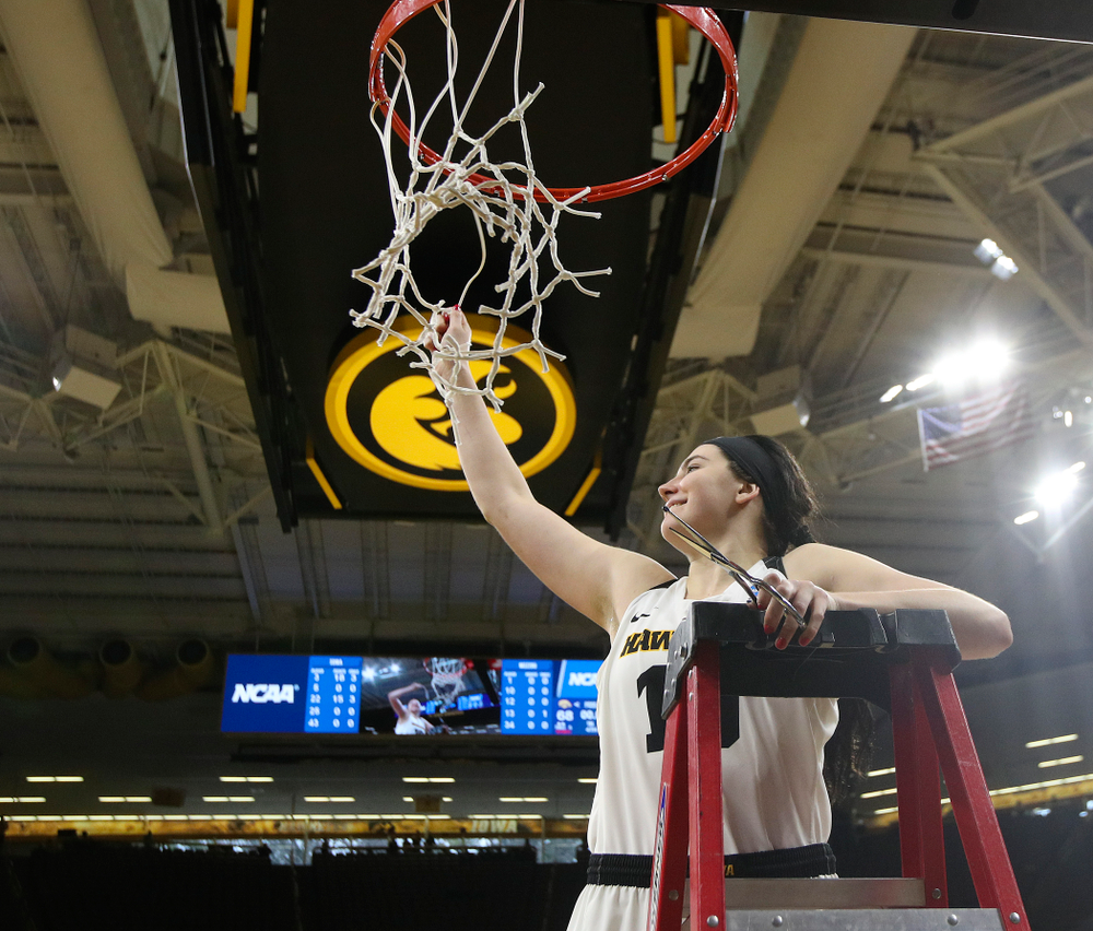 Iowa Hawkeyes center Megan Gustafson (10) cuts down the net after winning their second round game in the 2019 NCAA Women's Basketball Tournament at Carver Hawkeye Arena in Iowa City on Sunday, Mar. 24, 2019. (Stephen Mally for hawkeyesports.com)