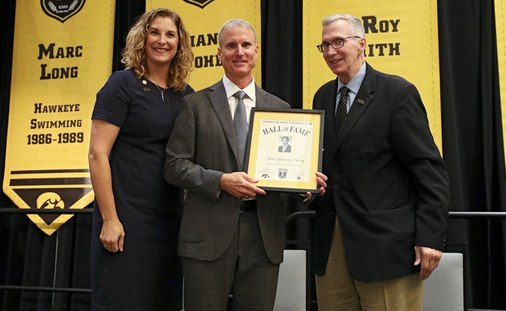 Barb Randall (from left), co-chair of the Varsity Club Advisory Committee, 2019 University of Iowa Athletics Hall of Fame inductee Marc Long, and Andy Piro, assistant athletics director and executive director of the Varsity Club, during the Hall of Fame Induction Ceremony at the Coralville Marriott Hotel and Conference Center in Coralville on Friday, Aug 30, 2019. (Stephen Mally/hawkeyesports.com)