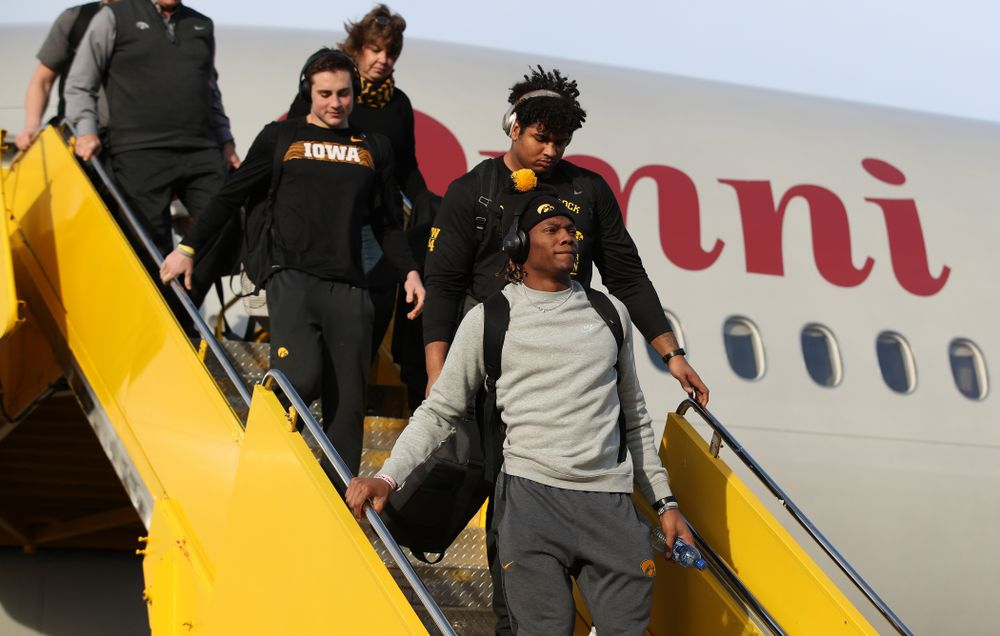 Iowa Hawkeyes wide receiver Brandon Smith (12) and offensive lineman Tristan Wirfs (74) disembark the team plane Wednesday, December 26, 2018 as they arrive in Tampa, Florida for the Outback Bowl. (Brian Ray/hawkeyesports.com)