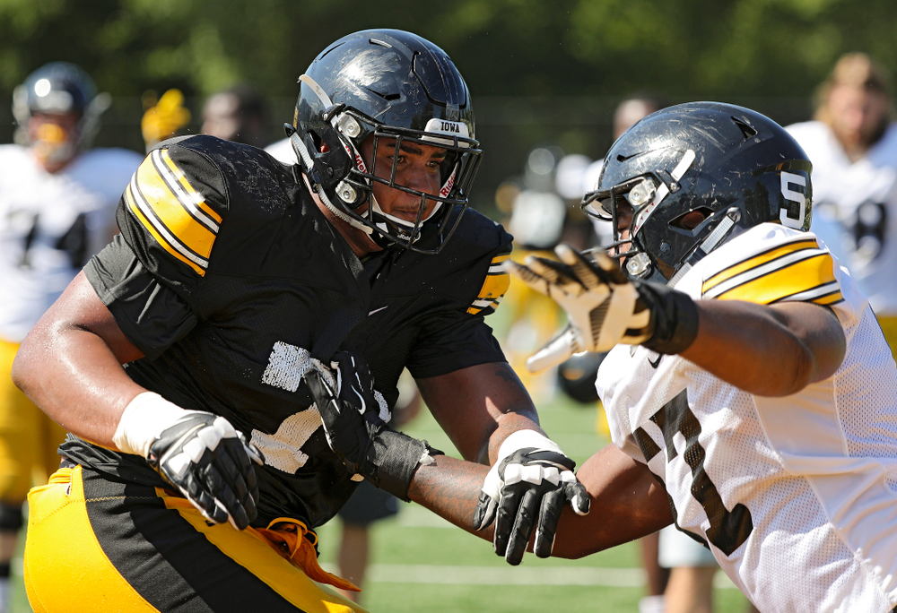 Iowa Hawkeyes offensive lineman Tristan Wirfs (74) and defensive end Chauncey Golston (57) run a drill during Fall Camp Practice #5 at the Hansen Football Performance Center in Iowa City on Tuesday, Aug 6, 2019. (Stephen Mally/hawkeyesports.com)