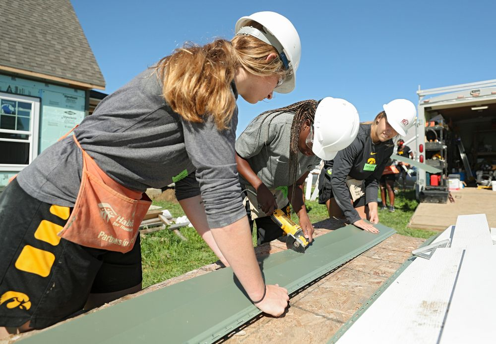 Iowa's Kate Martin (from left), Tomi Taiwo, and Kathleen Doyle work on cutting a piece of siding as they work on a Habitat for Humanity Women Build project in Iowa City on Wednesday, Sep 25, 2019. (Stephen Mally/hawkeyesports.com)