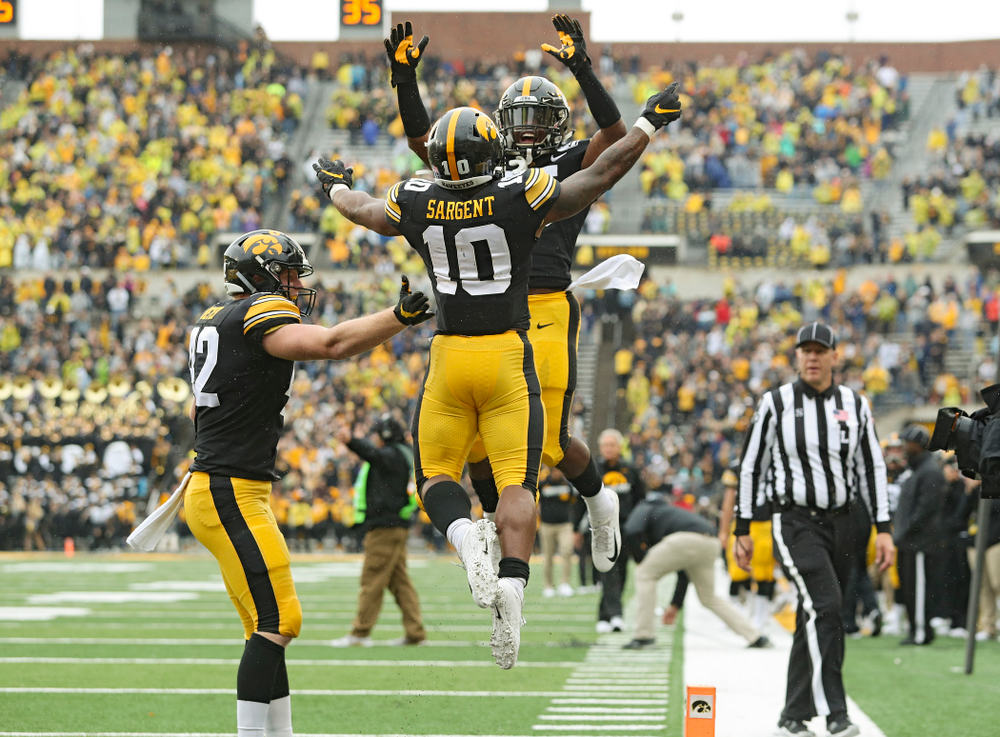 Iowa Hawkeyes running back Mekhi Sargent (10) celebrates his touchdown run with running back Tyler Goodson (15) and tight end Shaun Beyer (42) during the fourth quarter of their game at Kinnick Stadium in Iowa City on Saturday, Oct 19, 2019. (Stephen Mally/hawkeyesports.com)