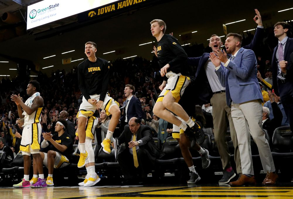 Iowa Hawkeyes guard Austin Ash (13), forward Michael Baer (0), forward Jack Nunge (2), and Jordan Bohannon celebrate on the bench against the Michigan Wolverines Friday, January 17, 2020 at Carver-Hawkeye Arena. (Brian Ray/hawkeyesports.com)
