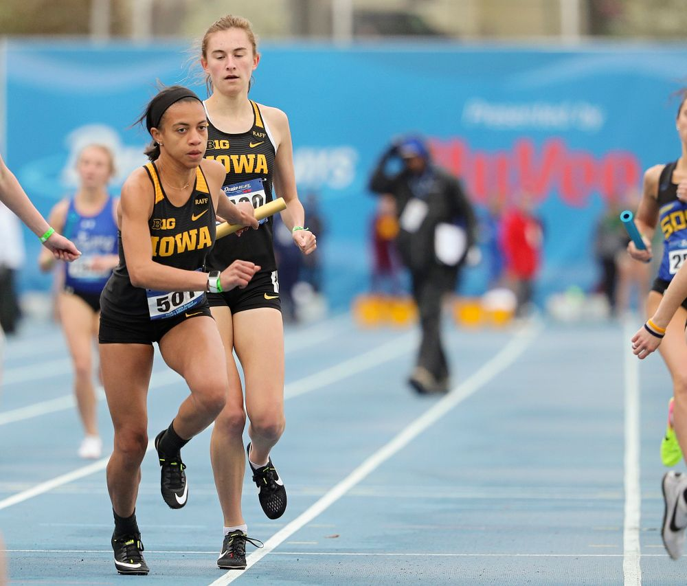 Iowa's Grace McCabe hands the baton off to Alexis Gay runs the women's distance medley relay event during the third day of the Drake Relays at Drake Stadium in Des Moines on Saturday, Apr. 27, 2019. (Stephen Mally/hawkeyesports.com)