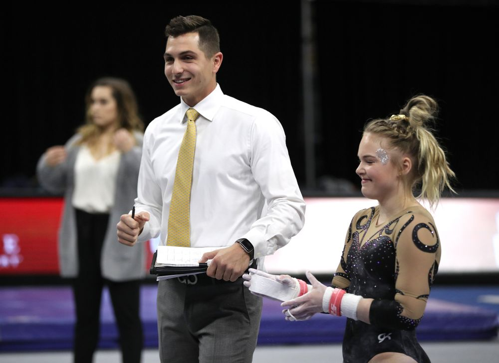 Iowa assistant coach Vince Smurro talks with Charlotte Sullivan before she competes on the bars during their meet against Southeast Missouri State Friday, January 11, 2019 at Carver-Hawkeye Arena. (Brian Ray/hawkeyesports.com)