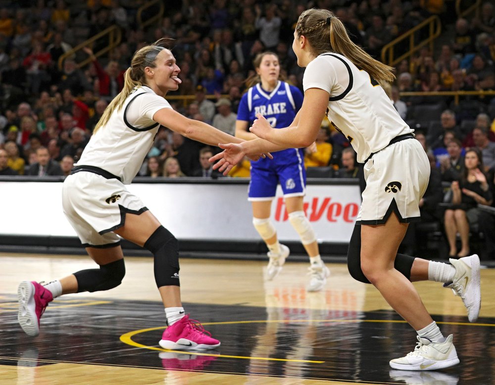 Iowa Hawkeyes guard Makenzie Meyer (3) slaps hands with guard Kathleen Doyle (22) after Doyle made a basket during the fourth quarter of their game at Carver-Hawkeye Arena in Iowa City on Saturday, December 21, 2019. (Stephen Mally/hawkeyesports.com)