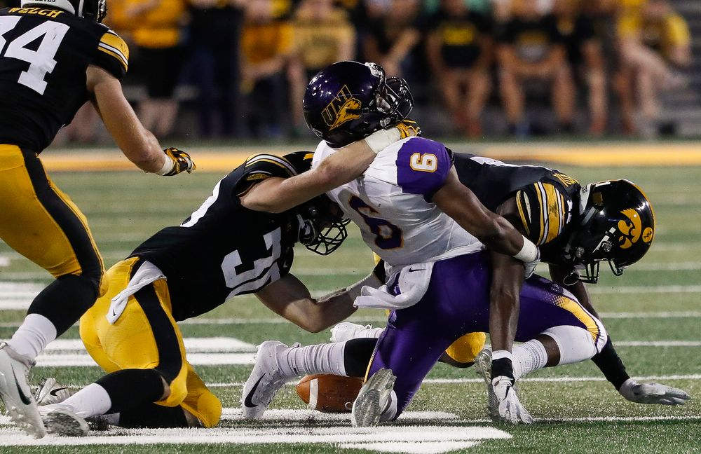 Iowa Hawkeyes defensive back Jake Gervase (30) and Iowa Hawkeyes defensive back Michael Ojemudia (11) combine to force a fumble during a game against Northern Iowa at Kinnick Stadium on September 15, 2018. (Tork Mason/hawkeyesports.com)