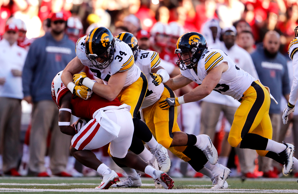 Iowa Hawkeyes linebacker Kristian Welch (34), running back Ivory Kelly-Martin (21), and defensive back Noah Clayberg (33)