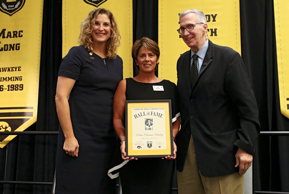 Barb Randall (from left), co-chair of the Varsity Club Advisory Committee, 2019 University of Iowa Athletics Hall of Fame inductee Deb Brickey, and Andy Piro, assistant athletics director and executive director of the Varsity Club, during the Hall of Fame Induction Ceremony at the Coralville Marriott Hotel and Conference Center in Coralville on Friday, Aug 30, 2019. (Stephen Mally/hawkeyesports.com)