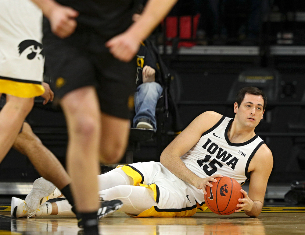 Iowa Hawkeyes forward Ryan Kriener (15) looks for someone to pass the ball to after diving for a loose ball on the court during the first half of their their game at Carver-Hawkeye Arena in Iowa City on Sunday, December 29, 2019. (Stephen Mally/hawkeyesports.com)