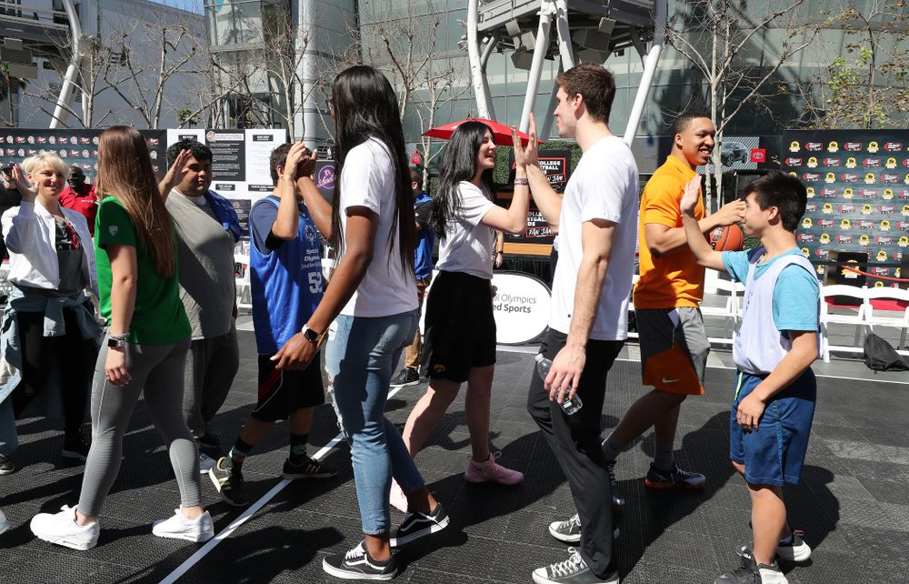Iowa Hawkeyes forward Megan Gustafson (10) high fives WisconsinÕs Ethan Happ during a Special Olympics event Friday, April 12, 2019 as part of the ESPN College Basketball Awards in the XBOX Plaza at LA Live.  (Brian Ray/hawkeyesports.com)