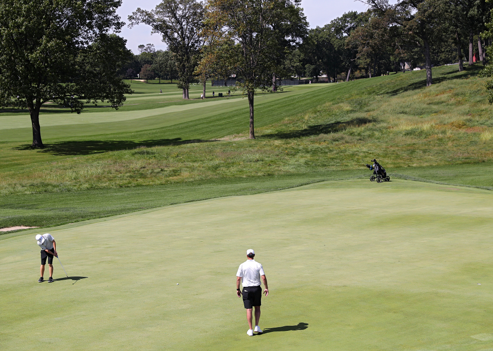 Iowa's Matthew Garside (from left) putts as head coach Tyler Stith looks on during the second day of the Golfweek Conference Challenge at the Cedar Rapids Country Club in Cedar Rapids on Monday, Sep 16, 2019. (Stephen Mally/hawkeyesports.com)