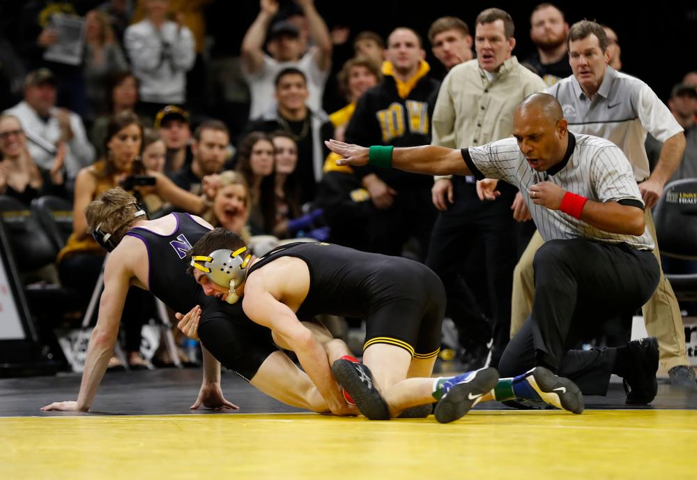 Iowa's Paul Glynn wrestles Northwestern's Colin Valdiviez at 133 pounds