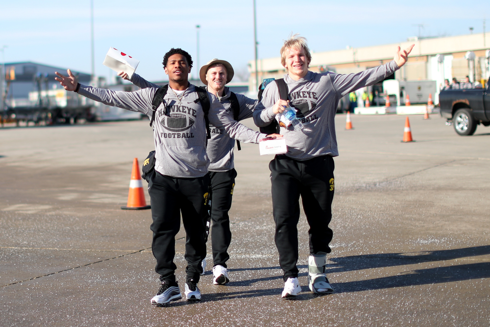 Iowa Hawkeyes wide receiver Tyrone Tracy Jr. (3), punter Michael Sleep-Dalton (22), and linebacker Monte Pottebaum (38) board the team plane at the Eastern Iowa Airport Saturday, December 21, 2019 on the way to San Diego, CA for the Holiday Bowl. (Brian Ray/hawkeyesports.com)