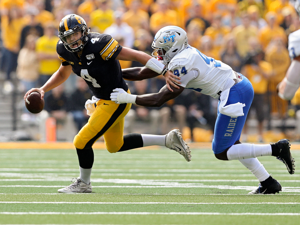 Iowa Hawkeyes quarterback Nate Stanley (4) pulls away from a defender during the second quarter of their game at Kinnick Stadium in Iowa City on Saturday, Sep 28, 2019. (Stephen Mally/hawkeyesports.com)