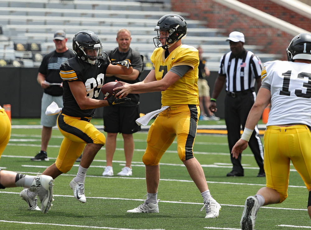 Iowa Hawkeyes wide receiver Nico Ragaini (89) takes a handoff from quarterback Spencer Petras (7) during Fall Camp Practice No. 8 at Kids Day at Kinnick Stadium in Iowa City on Saturday, Aug 10, 2019. (Stephen Mally/hawkeyesports.com)