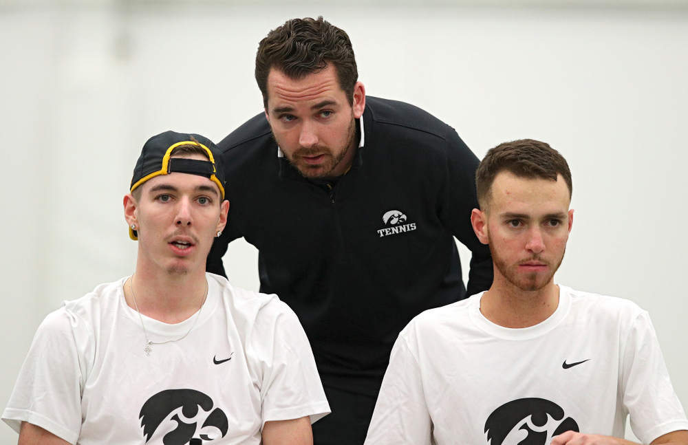 Mellecker Family Head Men's Tennis Coach Ross Wilson (center) talks with Nikita Snezhko (left) and Kareem Allaf (right) during their doubles match at the Hawkeye Tennis and Recreation Complex in Iowa City on Sunday, February 16, 2020. (Stephen Mally/hawkeyesports.com)
