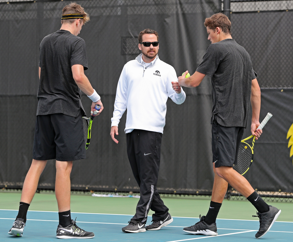 Iowa head coach Ross Wilson (center) talks with Nikita Snezhko (left) and Joe Tyler (right) during a double match against Ohio State at the Hawkeye Tennis and Recreation Complex in Iowa City on Sunday, Apr. 7, 2019. (Stephen Mally/hawkeyesports.com)