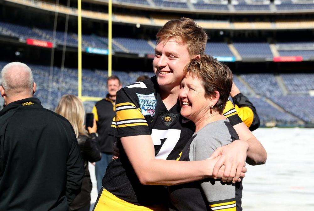Iowa Hawkeyes quarterback Spencer Petras (7) hugs his mother following the team photo Wednesday, December 25, 2019 at SDCCU Stadium in San Diego. (Brian Ray/hawkeyesports.com)
