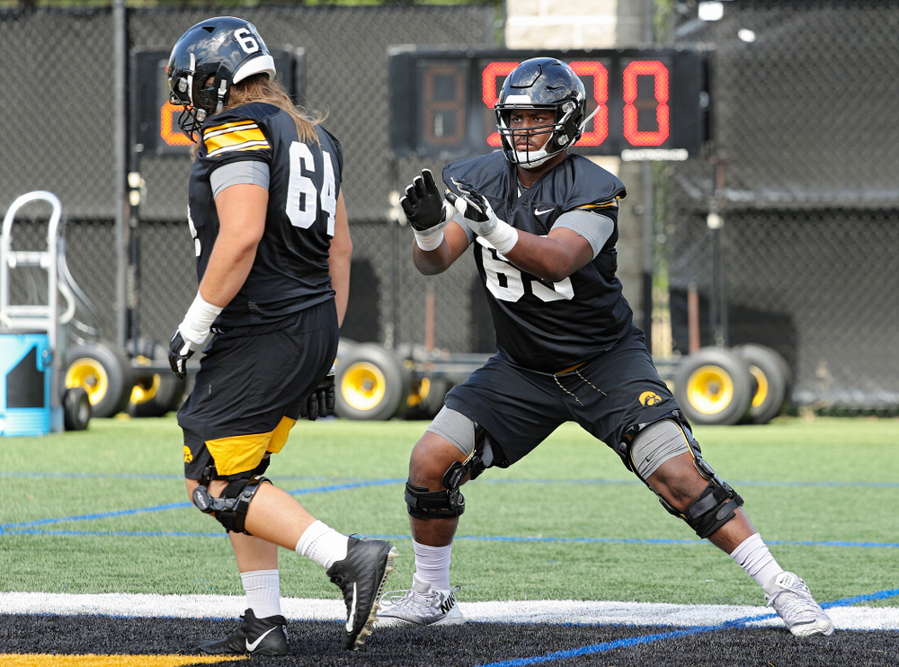Iowa Hawkeyes offensive lineman Kyler Schott (64) and offensive lineman Justin Britt (63) run a drill during Fall Camp Practice No. 13 at the Hansen Football Performance Center in Iowa City on Friday, Aug 16, 2019. (Stephen Mally/hawkeyesports.com)