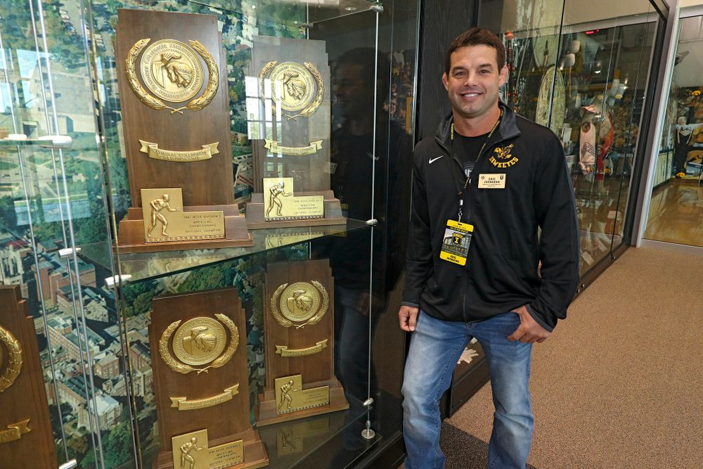 2019 University of Iowa Athletics Hall of Fame inductee Eric Juergens stands by some of the NCAA National Championship trophies he helped win at the University of Iowa Athletics Hall of Fame in Iowa City on Friday, Aug 30, 2019. (Stephen Mally/hawkeyesports.com)