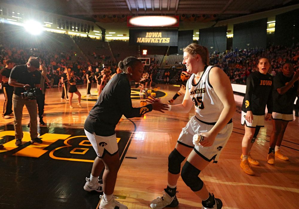 Iowa Hawkeyes guard Zion Sanders (21) shakes hands with forward Monika Czinano (25) as she is introduced before their game at Carver-Hawkeye Arena in Iowa City on Saturday, December 21, 2019. (Stephen Mally/hawkeyesports.com)