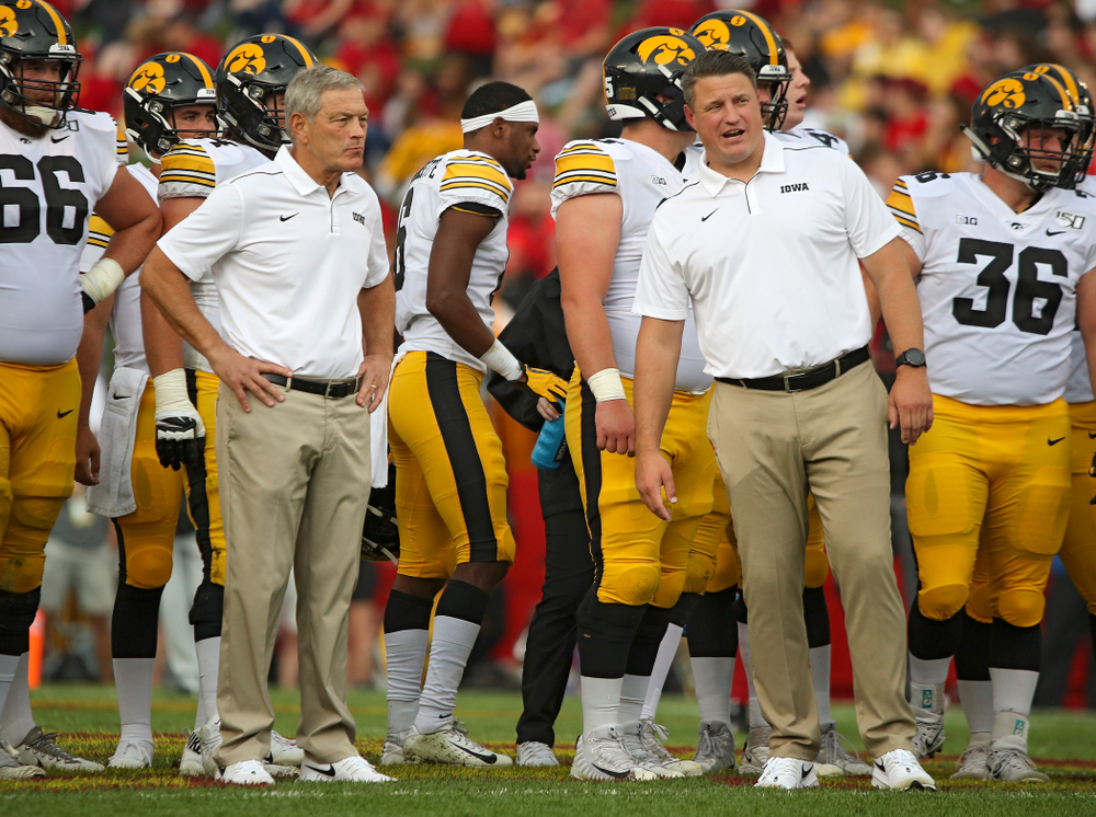 Iowa Hawkeyes head coach Kirk Ferentz (from left) talks with offensive coordinator Brian Ferentz as the team warms up after a weather delay during the first quarter of their Iowa Corn Cy-Hawk Series game at Jack Trice Stadium in Ames on Saturday, Sep 14, 2019. (Stephen Mally/hawkeyesports.com)