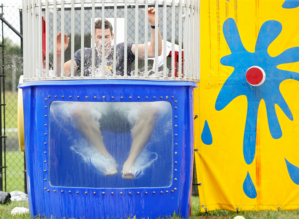 Iowa assistant strength and conditioning coach Cody Roberts drops into the water in the dunk tank during the Student-Athlete Kickoff outside the Karro Athletics Hall of Fame Building in Iowa City on Sunday, Aug 25, 2019. (Stephen Mally/hawkeyesports.com)