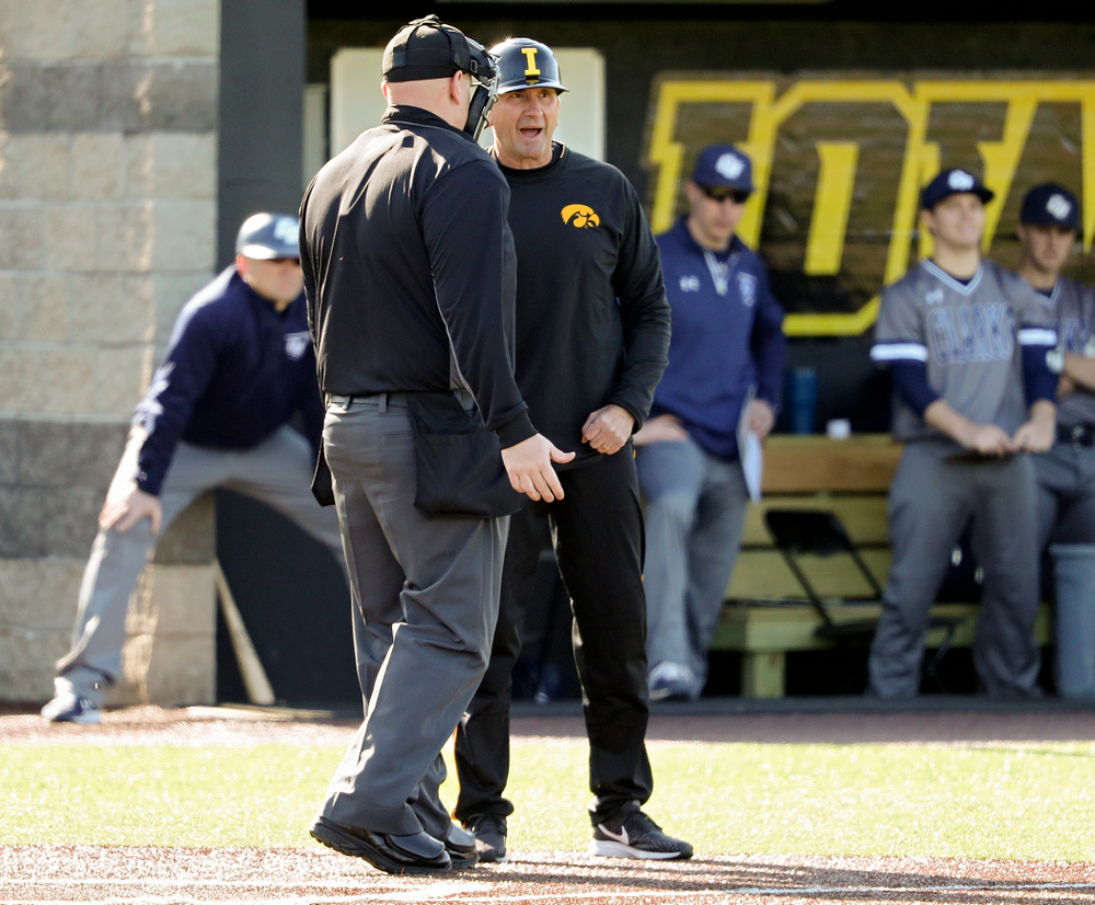 Iowa Hawkeyes head coach Rick Heller talks with the home plate umpire during the first inning of their game at Duane Banks Field in Iowa City on Tuesday, Apr. 2, 2019. (Stephen Mally/hawkeyesports.com)
