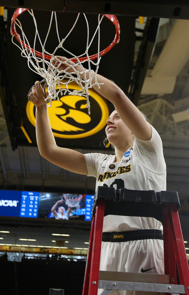 Iowa Hawkeyes guard Kathleen Doyle (22) cuts down the net after winning their second round game in the 2019 NCAA Women's Basketball Tournament at Carver Hawkeye Arena in Iowa City on Sunday, Mar. 24, 2019. (Stephen Mally for hawkeyesports.com)