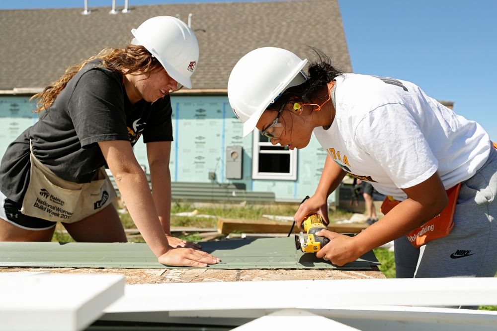 Iowa's McKenna Warnock (from left) and Alexis Sevillian work on cutting a piece of siding as they work on a Habitat for Humanity Women Build project in Iowa City on Wednesday, Sep 25, 2019. (Stephen Mally/hawkeyesports.com)