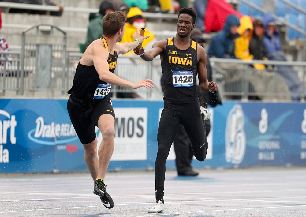 Iowa's Wayne Lawrence Jr. (right) hands off the baton to Noah Larrison as they run the men's 1600 meter relay event during the third day of the Drake Relays at Drake Stadium in Des Moines on Saturday, Apr. 27, 2019. (Stephen Mally/hawkeyesports.com)