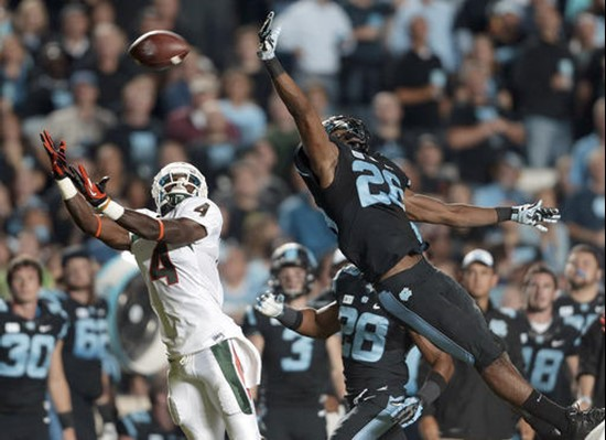Miami's Phillip Dorsett (4) reaches for a pass as North Carolina's Dominique Green (26) defends during the first half of an NCAA college football game...