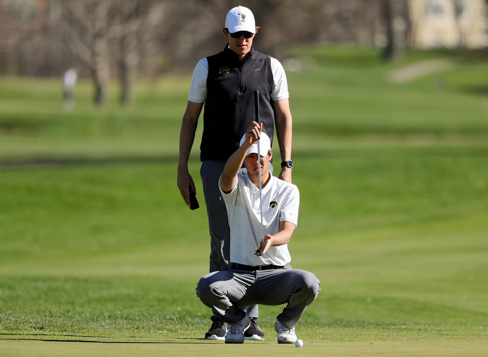 Iowa assistant coach Charlie Hoyle (top) stands above Joe Kim as he lines up a putt during the first round of the Hawkeye Invitational at Finkbine Golf Course in Iowa City on Saturday, Apr. 20, 2019. (Stephen Mally/hawkeyesports.com)