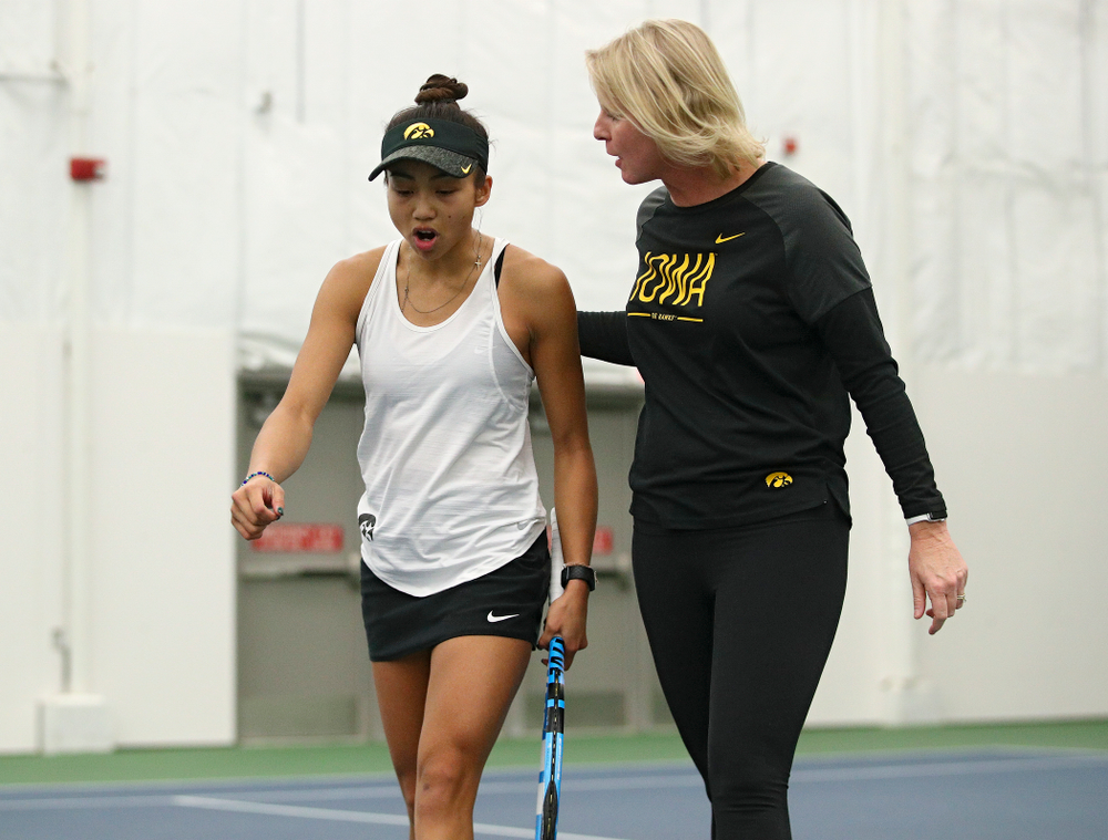 Iowa's Michelle Bacalla (from left) talks with Sasha Schmid after winning a game during her singles match at the Hawkeye Tennis and Recreation Complex in Iowa City on Sunday, February 23, 2020. (Stephen Mally/hawkeyesports.com)