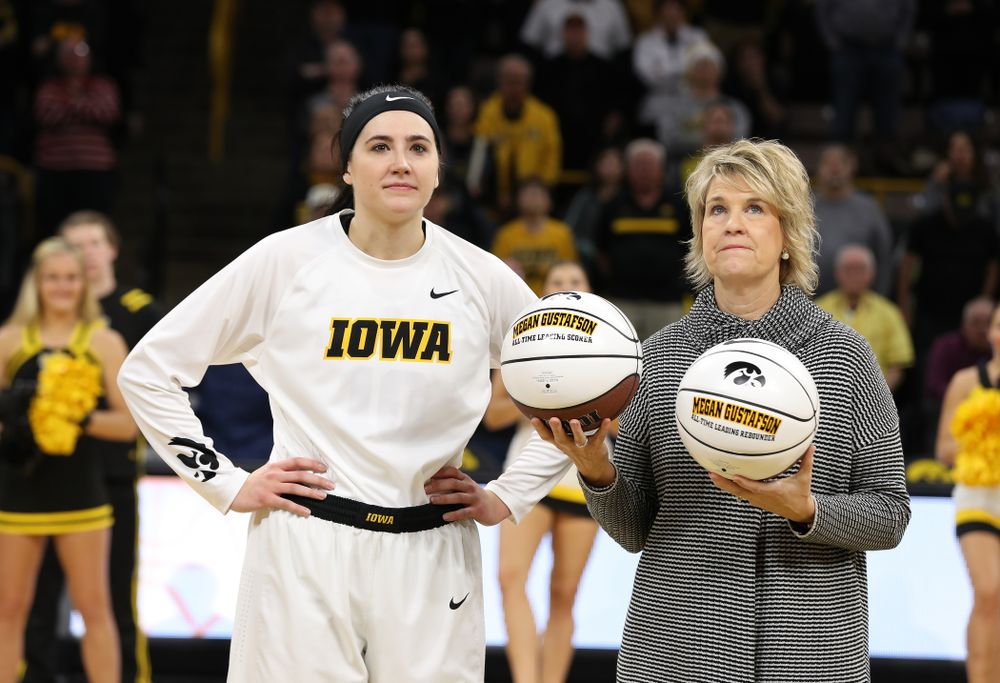 Iowa Hawkeyes forward Megan Gustafson (10) receives a pair of commemorative basketballs from head coach Lisa Bluder for becoming the school's all time rebounds leader and scoring leader before their gam eagainst the Nebraska Cornhuskers Thursday, January 3, 2019 at Carver-Hawkeye Arena. (Brian Ray/hawkeyesports.com)