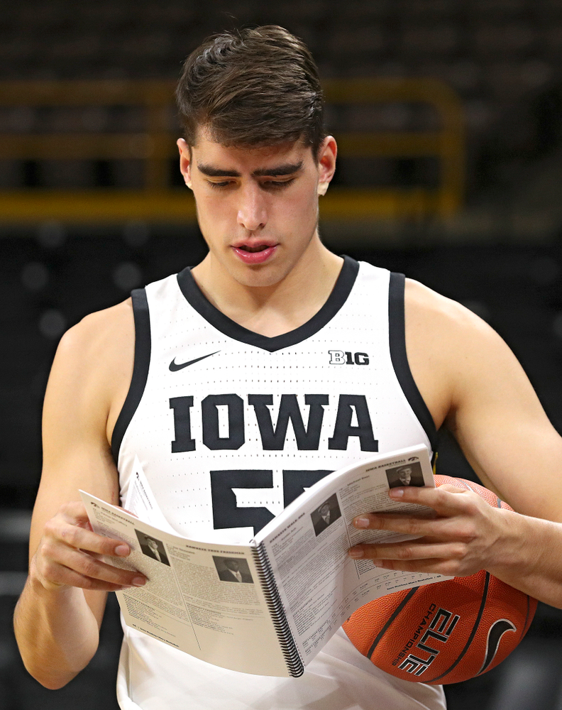 Iowa Hawkeyes forward Luka Garza (55) reads a media guide during Iowa Men's Basketball Media Day at Carver-Hawkeye Arena in Iowa City on Wednesday, Oct 9, 2019. (Stephen Mally/hawkeyesports.com)