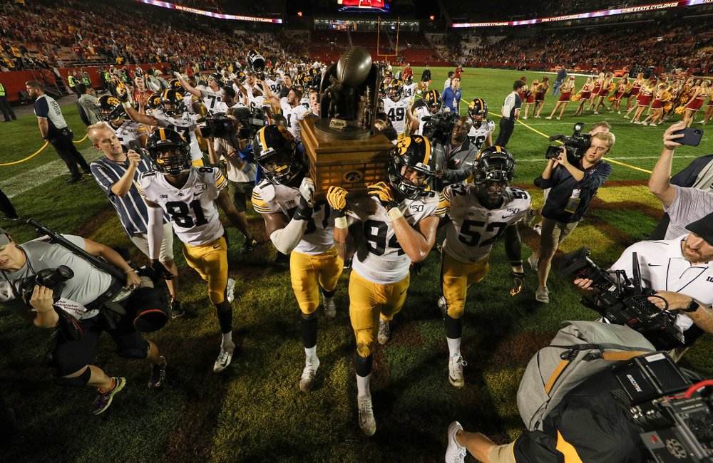 Iowa Hawkeyes defensive end Chauncey Golston (57) and defensive end A.J. Epenesa (94) celebrate with the Cy-Hawk trophy following their win over the Iowa State Cyclones Saturday, September 14, 2019 in Ames, Iowa. (Brian Ray/hawkeyesports.com)