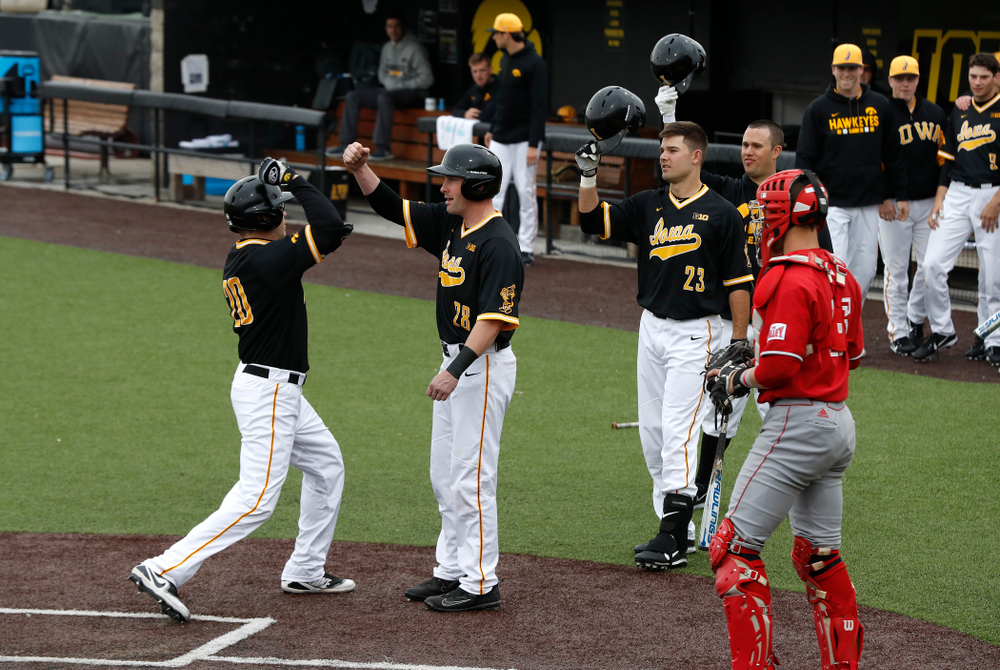 Iowa Hawkeyes catcher Austin Guzzo (20) first bumps infielder Chris Whelan (28) after hitting a home-run against the Bradley Braves Wednesday, March 28, 2018 at Duane Banks Field. (Brian Ray/hawkeyesports.com)